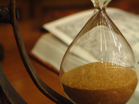 Photo of hourglass with book in background